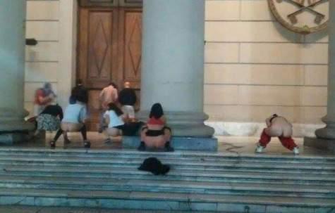 """Militantes de """"Podemos"""" orinando a la puerta de la catedral de la Almudena de Madrid."""