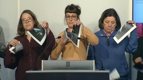 Diputadas de la CUP en el Parlament rompiendo fotografias del rey , Felipe VI., durante una rueda de prensa convocada hoy por la detencion de cinco jovenes independentistas que no se presentaron ante el juez de la Audiencia Nacional.